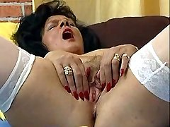 Old horny slut fucks herself in bed with dildo